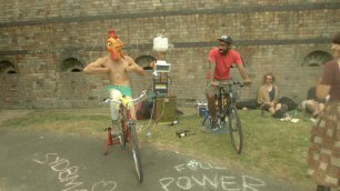 Chicken and friend riding a bicycle generator to power a sound system